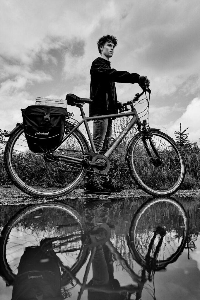 Ein männlicher Teenager steht an seinem Fahrrad mit Satteltasche