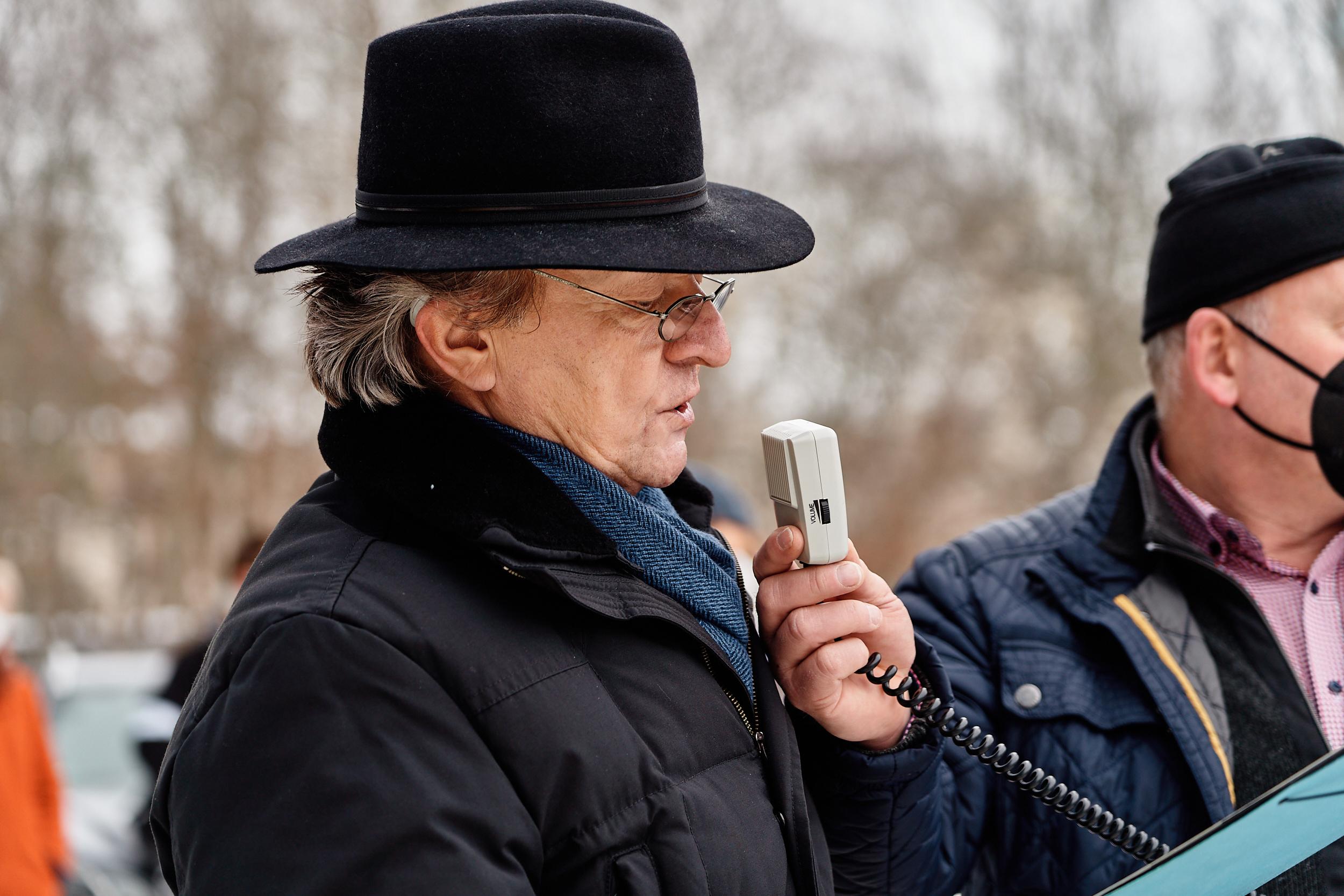 Ein Mann mit schwarzem Hut spricht während einer Kundgebung