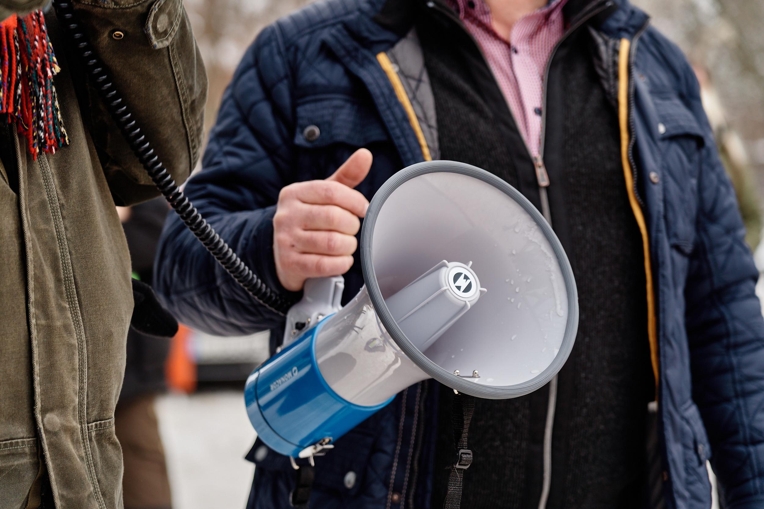Ein Megafon, gehalten von einem Mann in einer blauen Jacke