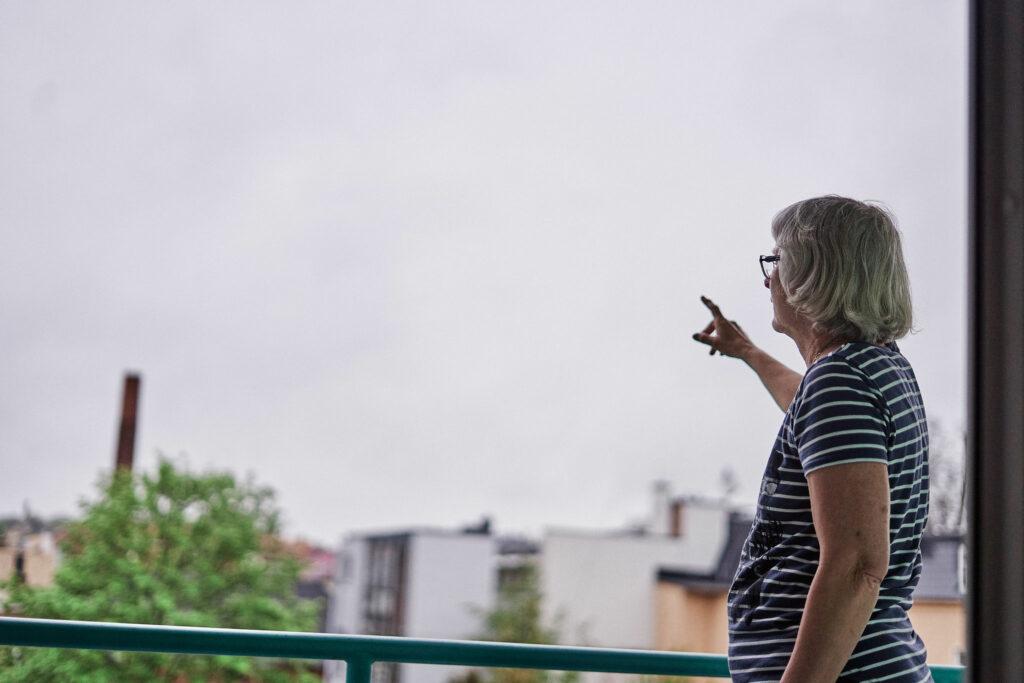 Alte Dame mit geringeltem Pulli steht auf einem Balkon und zeigt zum Himmel